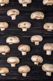 Draufsicht des champignons der frischen pilze lokalisiert auf dunklem hölzernem hintergrund