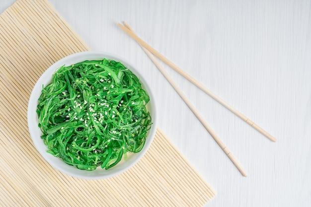 Draufsicht des chuka-wakame-seetang-salats mit sesam in der schüssel mit stäbchen auf bambusmatte