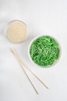 Draufsicht des chuka wakame seetang-salats mit sesam in der weißen schüssel mit bambusstäbchen