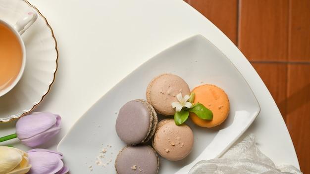 Draufsicht des couchtischs im wohnzimmer mit französischen bunten macarons und teetasse verziert mit tulpenblumen