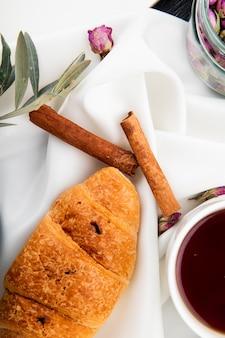 Draufsicht des croissants mit zimtstangen und einer tasse tee auf weiß