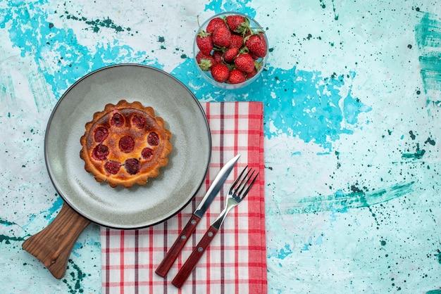 Draufsicht des cupcakes mit gebratener oberfläche und erdbeeren auf tischdecke