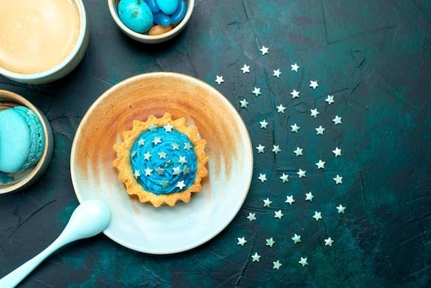 Draufsicht des cupcakes mit kühlen sternen und schattendekorationen auf dunkelblau,