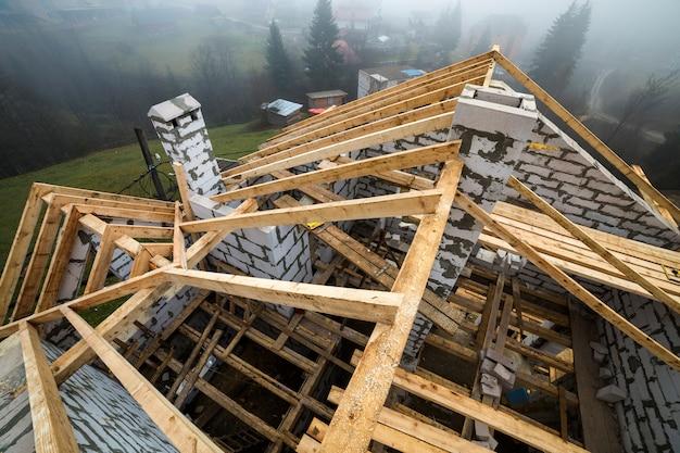 Draufsicht des dachrahmens von den hölzernen bauholzbalken und -planken auf den wänden hergestellt von den hohlschaumisolierungsblöcken.