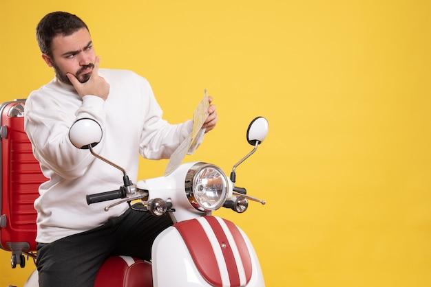 Draufsicht des denkenden kerls, der auf dem motorrad mit koffer darauf sitzt und karte auf isoliertem gelben hintergrund hält