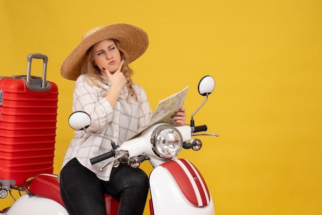 Draufsicht des denkens der jungen frau, die hut trägt und auf motorrad sitzt und karte hält, konzentrierte sich auf etwas auf gelb