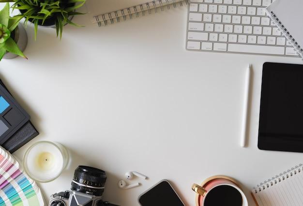 Draufsicht des designerarbeitstisches mit büromaterial und kopienraum auf weißem tischhintergrund