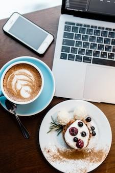 Draufsicht des designerplatzes. freiberuflicher arbeitsraum. notizbuch mit telefon, tasse kaffee