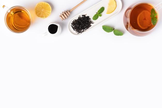 Draufsicht des designkonzepts von honigschwarztee mit gelber zitrone und minzblatt auf weißem tabellenhintergrund.