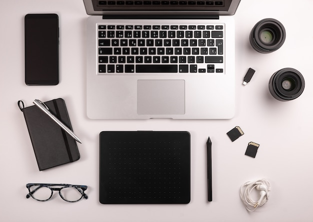 Draufsicht des desktops für fotografen oder designer, mit computer, tabelle, kaffee, notizbuch, mobile, speicherkarten
