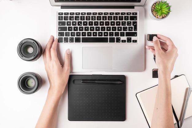 Draufsicht des desktops mit laptop, tabelle, notizbuch, speicherkarten.