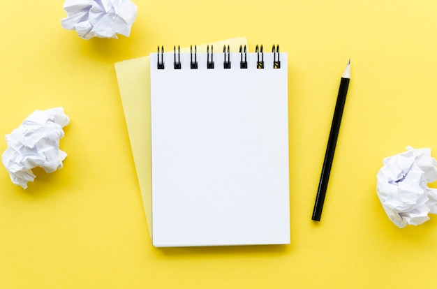 Draufsicht des desktops mit notizbuch und zerknittertem papier