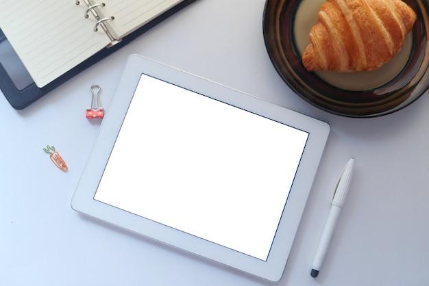 Draufsicht des digitalen tablets mit bürolieferanten auf tabelle.