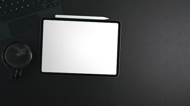 Draufsicht des digitalen tablets mit weißem bildschirm, kaffeetasse und eingabestift auf schwarzem leder.