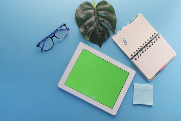 Draufsicht des digitalen tabletts mit bürolieferanten auf blauem hintergrund.