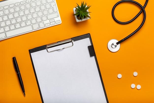 Draufsicht des doktors schreibtisch mit stethoskoptastaturnotizblock und stift, verordnung und pillen