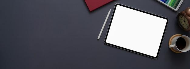Draufsicht des dunklen konzeptschreibtischs mit modell-tablette, verbrauchsmaterial, kaffeetasse und kopienraum