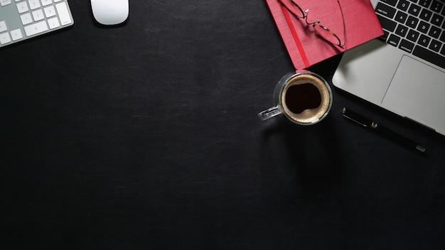 Draufsicht des dunklen ledernen schreibtischs mit laptop-computer und büroartikeln