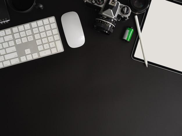 Draufsicht des dunklen modernen arbeitsbereichs mit tastatur und büromaterial auf schwarzem tisch mit kopierraum