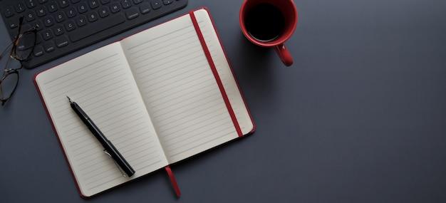 Draufsicht des dunklen modernen arbeitsplatzes mit offenem notizbuch und roter kaffeetasse