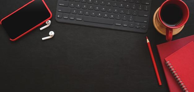Draufsicht des dunklen modernen arbeitsplatzes mit rotem büroartikel und kopienraum auf schwarzer tabelle