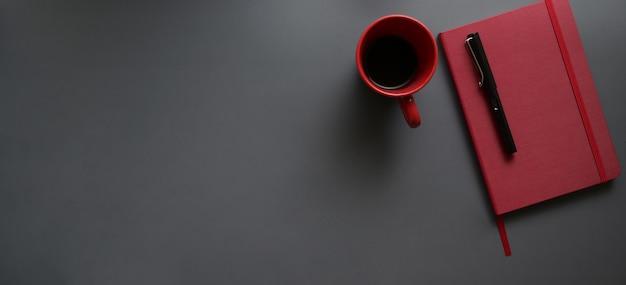 Draufsicht des dunklen modernen arbeitsplatzes mit rotem notizbuch und roter kaffeetasse auf dunkelgrauem schreibtisch