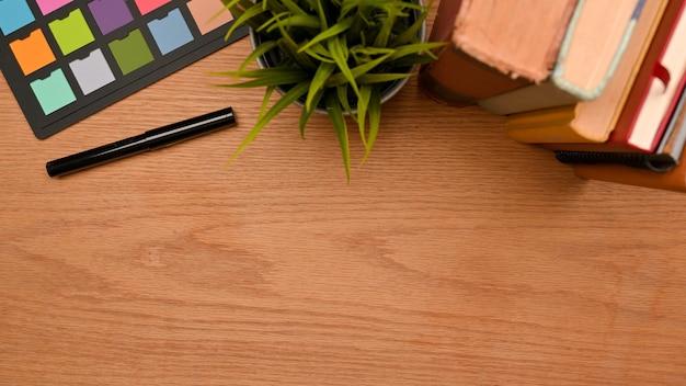 Draufsicht des einfachen arbeitsbereichs auf holztisch mit kopienraumstapel von büchern farbprüfer