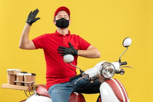Draufsicht des emotionalen jungen erwachsenen, der rote bluse und huthandschuhe in der medizinischen maske trägt, die ordnung liefert, die auf roller sitzt, der hoffnungsvoll fühlt