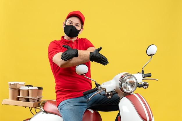 Draufsicht des emotionalen jungen erwachsenen, der rote bluse und huthandschuhe in der medizinischen maske trägt, die ordnung liefert, die auf roller sitzt, der jemanden begrüßt