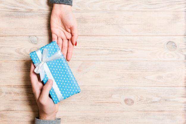 Draufsicht des empfangens eines geschenkes auf hölzernem hintergrund