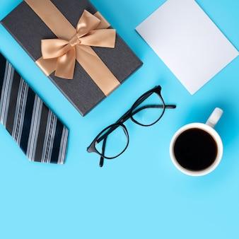 Draufsicht des entwurfskonzepts der geschenkidee des vatertags mit dem weißen leeren modell des grußes auf blauem tabellenhintergrund.