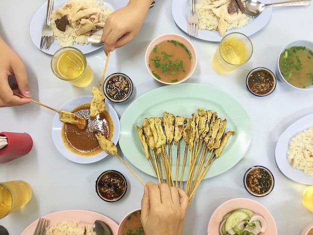 Draufsicht des familienmittagessens umfassen hühnerreissatz und satay-schweinefleischstock - glückliches mahlzeitkonzept der asiatischen draufsicht