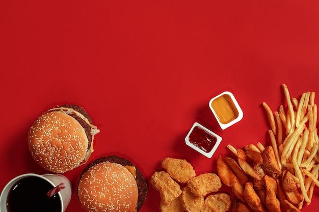 Draufsicht des fast-food-gerichts. fleischburger, kartoffelchips und glas getränk auf rotem grund. zusammensetzung zum mitnehmen. eingewickelte pommes-frites, hamburger, mayonnaise und ketchup-saucen auf rotem schreibtisch. platz kopieren