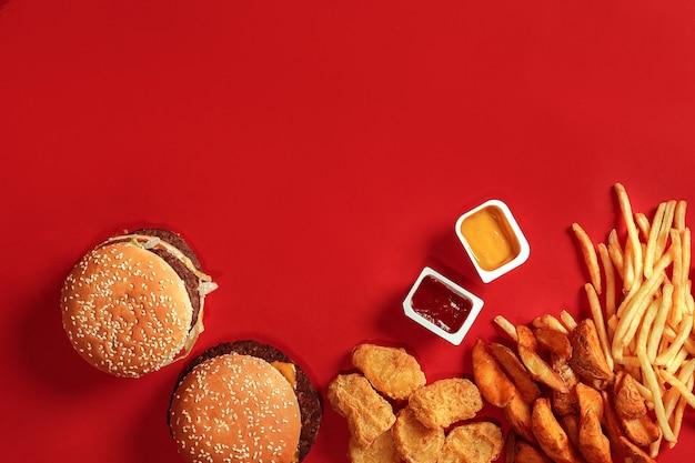 Draufsicht des fast-food-gerichts. fleischburger, kartoffelchips und nuggets auf rotem grund. zusammensetzung zum mitnehmen. eingewickelte pommes-frites, hamburger, mayonnaise und ketchup-saucen auf rotem schreibtisch. platz kopieren