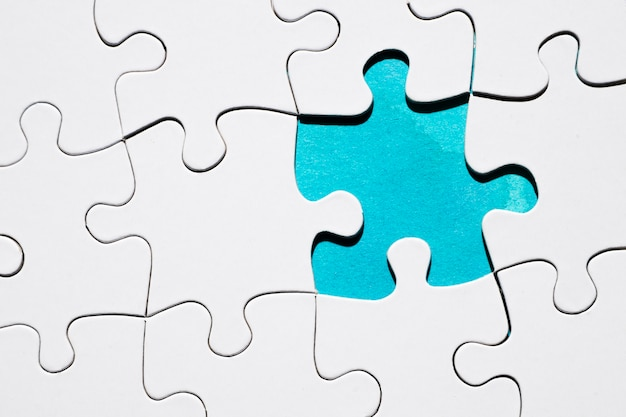 Draufsicht des fehlenden puzzlespielstückes auf puzzlespielgitterhintergrund