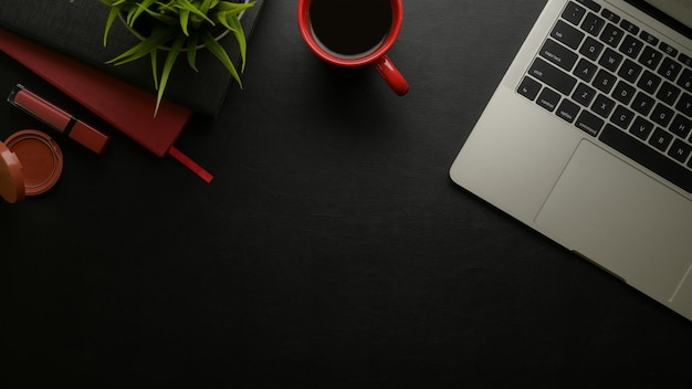 Draufsicht des femininen stilvollen schreibtischs mit kopierraum, laptop, kaffeetasse, zeitplanbücher, kosmetik und dekoration
