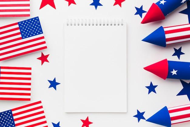 Draufsicht des feuerwerks für unabhängigkeitstag mit amerikanischen flaggen und notizbuch
