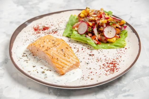 Draufsicht des fischmehls und des salats auf einem teller auf befleckter weißer oberfläche