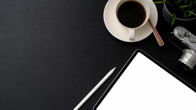 Draufsicht des fotografenarbeitsbereichs mit leerem bildschirmtablett, kamera, kaffeetasse und kopierraum