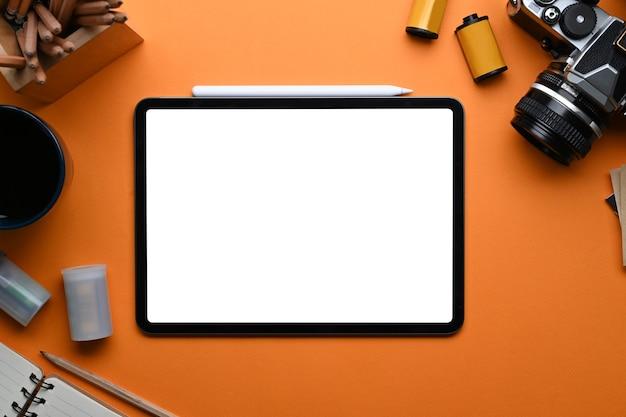 Draufsicht des fotografenarbeitsplatzes mit digitalem tablet, kamera, notebook und zimmerpflanze auf orangem hintergrund.