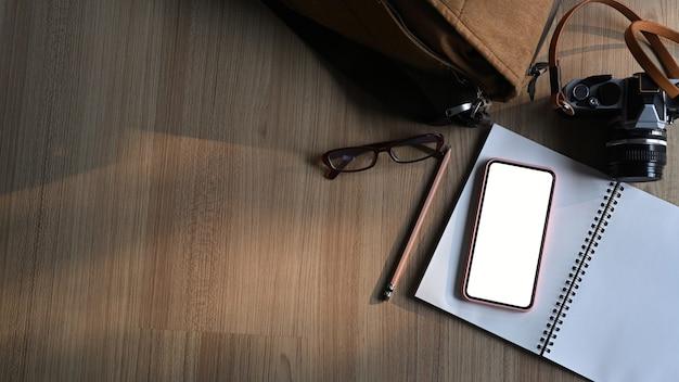 Draufsicht des fotografenarbeitsplatzes mit kamera, notizbuch, smartphone mit leerem bildschirm und kopierraum.
