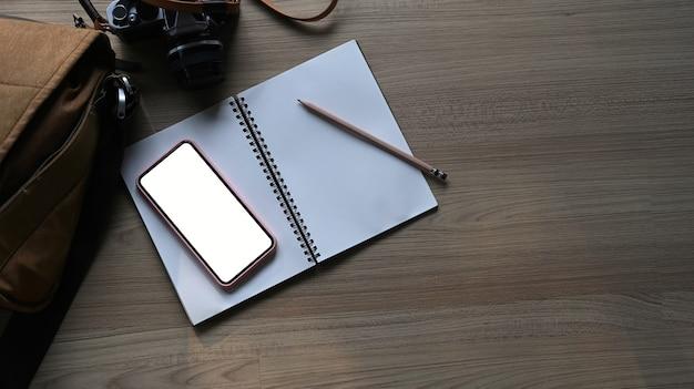 Draufsicht des fotografenarbeitsplatzes mit mock-up-handy, notizbuch und kamera auf holztisch. leerer bildschirm für die montage der grafikanzeige.