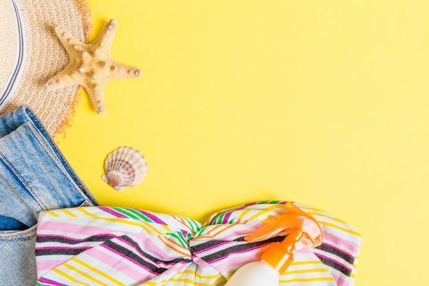 Draufsicht des frauen-sommeroutfits auf blauem gelbem hintergrund. modeurlaubskonzept