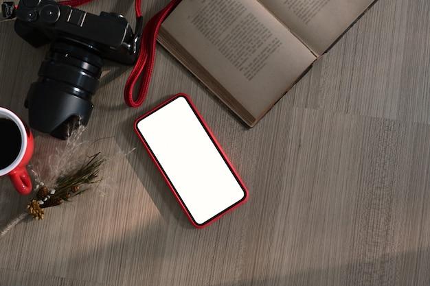 Draufsicht des freiberuflichen arbeitsplatzes mit kamera, notizbuch, smartphone mit leerem bildschirm für grafikanzeigemontage.