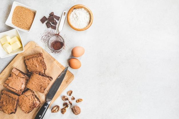 Draufsicht des frisch gebackenen hausgemachten brownie-kuchens angeordnet mit rezeptbestandteilen auf weißem rustikalem.