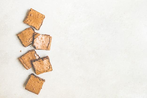 Draufsicht des frisch gebackenen hausgemachten brownie-kuchens, der in quadrate auf weißem rustikal geschnitten wird.