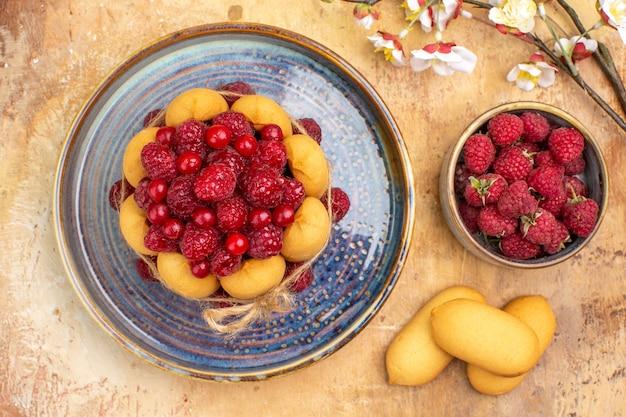 Draufsicht des frisch gebackenen weichen kuchens mit früchten und keksen auf mischfarbtabelle