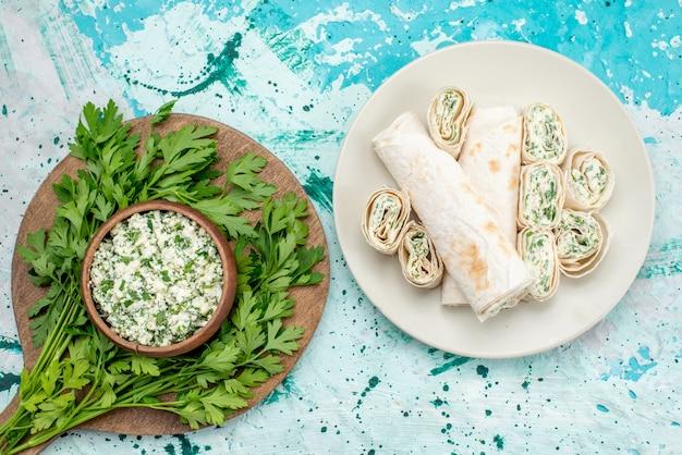Draufsicht des frisch geschnittenen kohlsalats mit grüns innerhalb der braunen schüssel und mit gemüserollen auf hellblauem schreibtisch, frischsnack des gemüsesalats