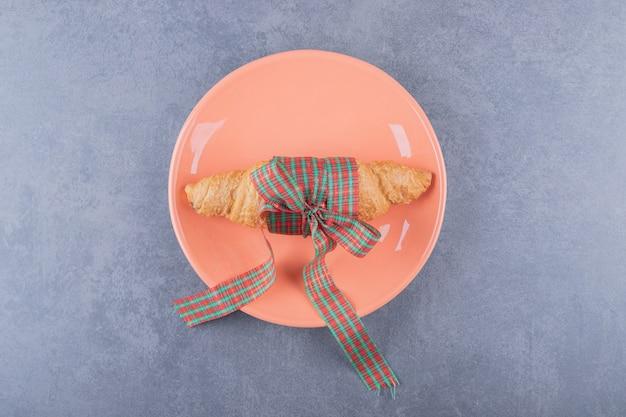 Draufsicht des frischen croissants auf orange platte.