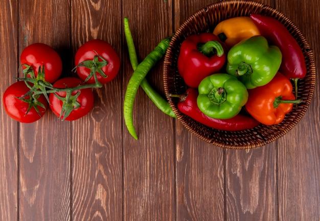 Draufsicht des frischen gemüses bunte paprikaschoten rote chilischoten in einem weidenkorb und frischen reifen tomaten auf holz rustikal